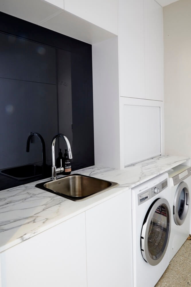 Small white laundry renovation ideas with white marble bench top finish