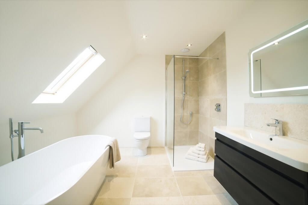 Modern white bathroom in attic, with sandstone colour tiles and black doors
