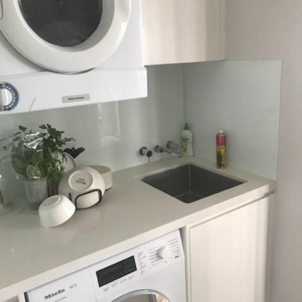 White and cream modern small laundry with white splashback